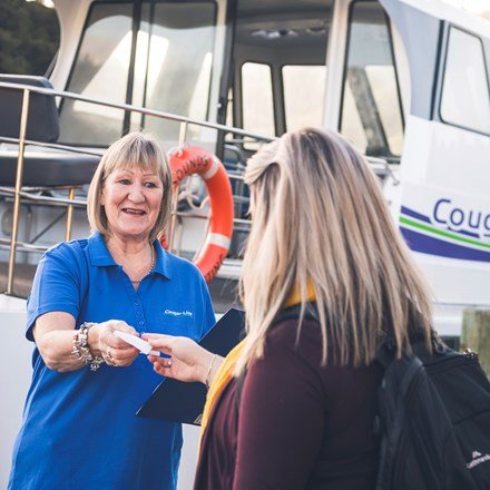 A passenger is greeted by a smiling Cougar Line staff member while boarding in Picton in the Marlborough Sounds, New Zealand.