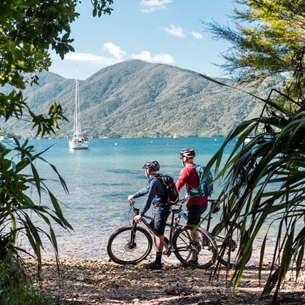 Two male bikes parked on the beach just off the Queen Charlotte Track with a yacht and the Marlborough Sounds behind.