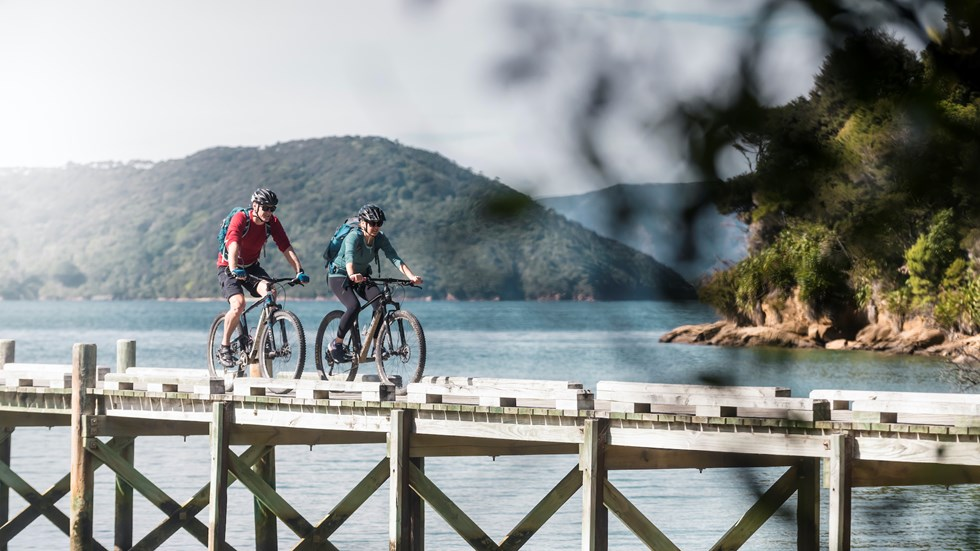 A male and female biking along the Ship Cove/Meretoto jetty at the start of the Queen Charlotte Track