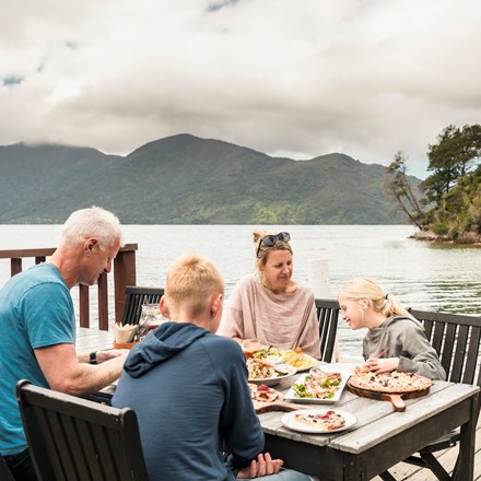 A family dining on the jetty at Punga Cove - a great way to enjoy stone baked pizza and more at the Boatshed Cafe and Bar.