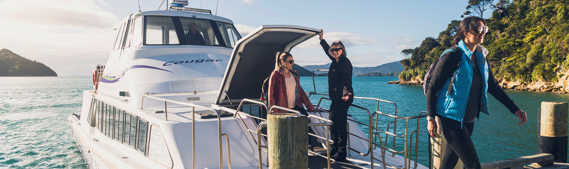 Two walkers disembarking from the Cougar Line boat at Ship Cove/Meretoto ready to walk on the Queen Charlotte Track.