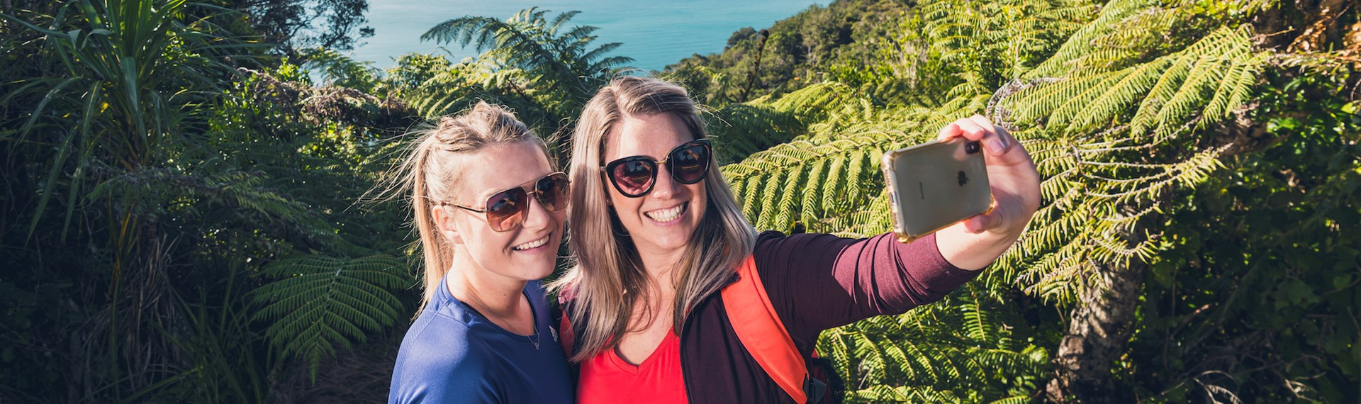 Two women take selfies at the lookout with Motuara Island in the background on the Queen Charlotte Track.